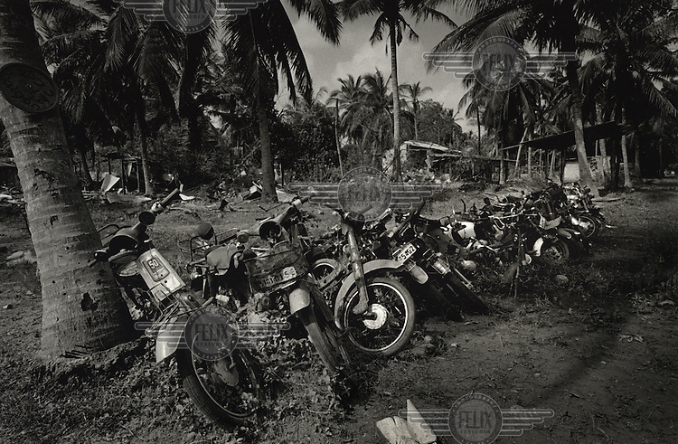 Motorcycles parked on the side of a street. 90% of the people displaced during the war have now returned. MAG (Mines Advisory Group) is now working in the last area to be resettled which is where the final stage of the conflict took place. It is a very eerie area with no people - just a few soldiers, heards of grazing cows that have gone wild, and rows of abandoned vehicles. The area is utterly destroyed.