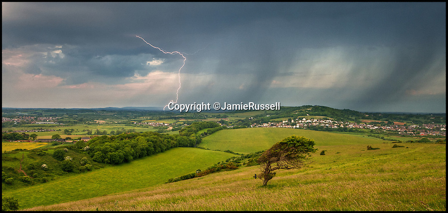 BNPS.co.uk (01202 558833)<br /> Pic: JamieRussell/BNPS<br /> <br /> ***Please Use Full Byline***<br /> <br /> A storm gathers over Culver Down on the Isle of Wight.<br /> <br /> Stunning photographs have revealed a turbulent side to the normally genteel Isle of Wight.<br /> <br /> The seemingly benign south coast holiday destination has been catalogued over a stormy year by local photographer Jamie Russell, and his astonishing pictures reveal the dramatic changes in weather that roll across the UK in just 12 months.<br /> <br /> Lightning storms, ice, floods, gales and blizzards have all been captured by the intrepid photographer who frequently got up in the middle of the night to capture the climatic chaos.<br /> <br /> Looking at these pictures prospective holidaymakers could be forgiven for thinking twice about a gentle staycation on the south coast island.