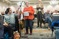 "Susan Carpenter, of South Dennis, Mass., speaks at a public hearing regarding Pilgrim Station, a nuclear power plant run by Entergy, at Hotel 1620 in Plymouth, Massachusetts, USA, on Tues., Jan. 31, 2017. Carpenter is the Secretary of the Cape Downwinders, a group opposed to the continued operation of Pilgrim Station. Carpenter expressed her concerns about the safety of the plant. An email from the NRC was leaked in December 2016 outlining problems with the ""safety culture"" at the plant and an ""overwhelmed"" staff. Area residents have been calling for the plant to be shut down. The green signs in the audience, reading ""Shut Pilgrim Now,"" are from a group of area residents calling for the plant's closure called Cape Downwinders."