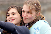 Two middle school students take a self-portrait during a digital photography class