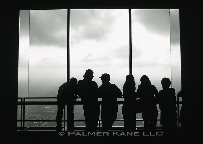 Silhouette of group of people looking out window of Sears Tower, Chicago, USA