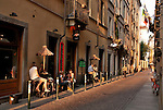 People sit at outdoor tables at a restaurant on a narrow, cobble stone street in Turin, Italy
