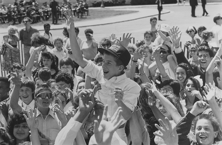 "A teenage boy with braces and Hopkins Lacrosse cap on is lifted above the crowd to wave ""goodbye"" to the Queen as well as to get his face on Television, on May 20, 1991. (Photo by Laura Patterson/CQ Roll Call via Getty Images)"