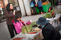 A woman and her daughter look at vegetables on display on a stall installed on the sidewalk on Spadina avenue in Toronto Chinatown April 23, 2010. Toronto Chinatown is an ethnic enclave in Downtown Toronto with a high concentration of ethnic Chinese residents and businesses extending along Dundas Street West and Spadina Avenue.