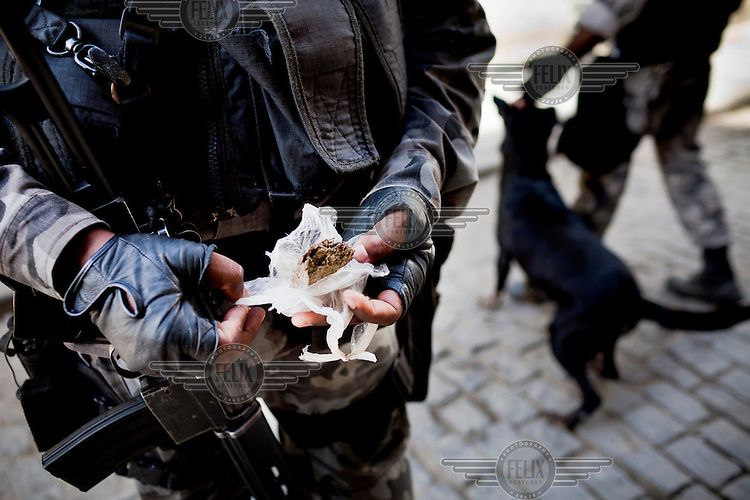 Heavily armed special police officer shows a bag of cannabis found during a patrol in Complexo da Mare near Rio de Janeiro's international airport. The favela consists of a complex of 16 communities, in the north zone of Rio de Janeiro. It is the largest complex of favelas, housing 130,000 residents. It is targeted for pacification as the city prepares for the 2014 World Cup and the 2016 Olympics.