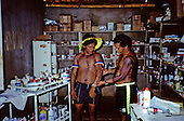 Gorotire, Xingu, Brazil. Kayapo man trained as auxiliary nurse advising a patient in the medical centre.