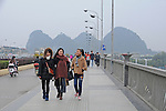 3 smiling young women walk across the Independence Bridge, over the Li River, in Guilin, China.  The regional distinctive mountains loom in rear