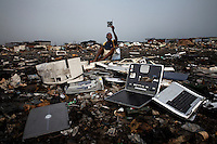 Discarded laptops lie on the ground at Agbogbloshie dump, which has become a dumping ground for computers and electronic waste from all over the developed world. Hundreds of tons of e-waste end up here every month. It is broken apart, and those components that can be sold on, are salvaged.
