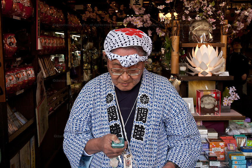A festival supporter checks email on his cellphone during the Kanamara matsuri or festival of the iron phallus in Kawasaki Daishi near Tokyo, Japan. Sunday April 1st 2012
