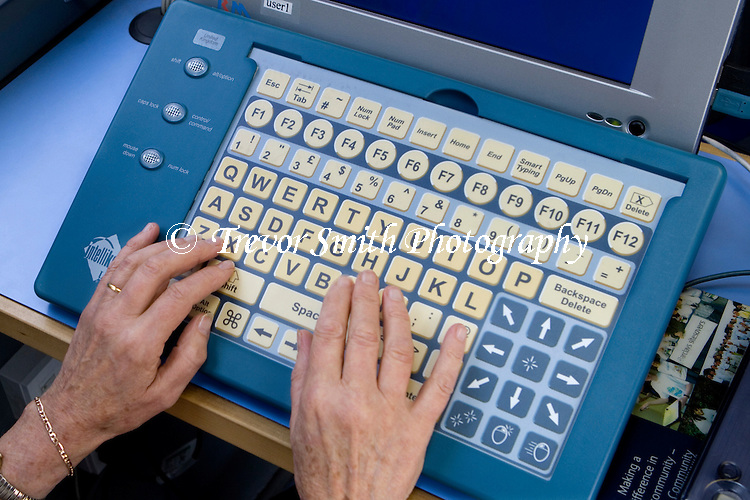 A pensioner using a specialised IntelliKeys large keyboard while learning computer skills