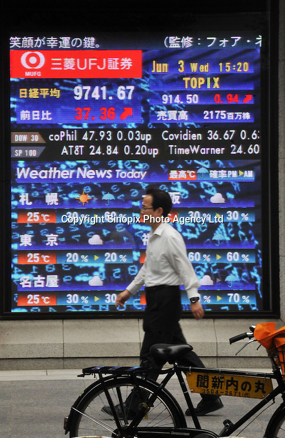 People pass a stock board in the Otemachi business district of Tokyo.  .