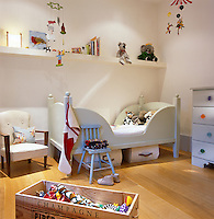 A contemporary child's bedroom with a modern wooden cot and plenty of storage