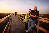 An older couple stand together on a pathway / bridge in a wetlands area.