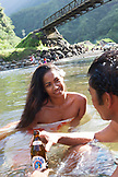 FRENCH POLYNESIA, Tahiti. A local swiming hole close to the town of Papenoo along a dirt road towards the center of the island. A local couple swimming in the water.