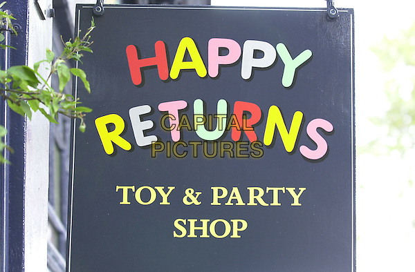 """HAPPY RETURNS TOY & PARTY SHOP.Where Pierce Brosnan was shopping with wife (inside shop, in red)  and son """" and where they bought a Lego Star Wars toy..*Exclusive*.*Fees must be agreed before use*.© Capital Pictures.www.capitalpictures.com.tel +44 (0)20 7253 1122.sales@capitalpictures.com"""