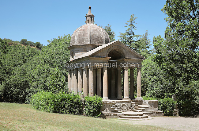 Templo de Vignola or Temple of Eternity, a memorial to Giulia Farnese, wife of Pier Francesco Orsini, at the summit of the Garden of Bomarzo, also known as the Sacro Bosco or Sacred Grove, or the Parco dei Mostri or Park of the Monsters, a monumental Mannerist park complex, c. 1550, made by Pier Francesco Orsini, or Vicino, 1523–1585, Duke of Orsini, designed by Pirro Ligorio, 1512-83, with sculptures by Simone Moschino, 1533-1610, in Bomarzo, Viterbo, Lazio, Italy. The temple is octagonal topped by a cupola and bell, with a square colonnaded portico, in a mixture of Greek, Classical and Renaissance styles. The temple houses the tombs of Giovanni Bettini and Tina Severi, the owners who restored the garden in the 20th century. The gardens are in a wood at the bottom of a valley beneath the Castle of Orsini, with many large sculptures, small buildings and inscribed poems. The layout of the garden is chaotic, in contrast with formal Renaissance gardens, and it has a surrealistic air. The garden was restored in the 1970s and is now a major tourist attraction. Picture by Manuel Cohen