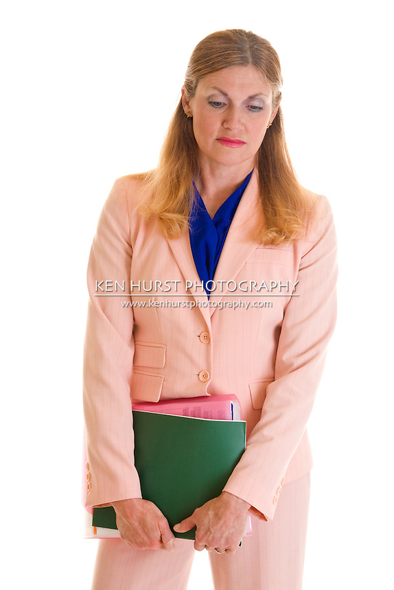 Solemn, beautiful, middle-aged blonde executive business woman in a pink business suit.