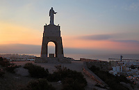 The statue of the Sacred Heart of Jesus, built in the 1930s at the top of Cerro San Cristobal, San Cristobal Hill or Monte Laham, with the port of Almeria in the distance, in the Alcazaba, a 10th century fortified enclosure and royal residence in Almeria, Andalusia, Southern Spain. The Alcazaba was begun in 955 by Rahman III and completed by Hayran, Taifa king of Almeria, in the 11th century. It was later added to by the Catholic monarchs. Picture by Manuel Cohen