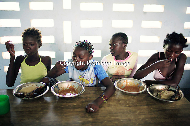 KINSHASA, DEMOCRATIC REPUBLIC OF CONGO - JULY 4: Unidentified girls eat lunch at a yearly summer camp run by Orper, a local NGO on July 4, 2006 in N Djili outside Kinshasa, Congo, DRC. The NGO has several shelters for homeless boys and girls in Kinshasa and has a program that reunites children with their families. The capital has a growing problem with children displaced by war, poverty and many has been rejected by their families and forced on the streets. About 15,000 children are estimated to live on the streets of Kinshasa. About fifty girls got to spend a week relaxing, playing, swimming eating three meals a day. Most important of all, it took them off the hard streets of Kinshasa, where they are often abused, take drugs and forced into prostitution. Congo, DRC is in ruins after forty years of mismanagement by the corrupt dictator and former president Mobuto Sese Seko. He fled the country in 1997 and a civil war started. The country is planning to hold general elections by July 2006, the first democratic elections in forty years. (Photo by Per-Anders Pettersson)