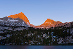 Sunrise first light glows on the mountains of an unnamed pass that leads to Royce Lake as seen looking across Honeymoon Lake in the high sierras east of Bishop California,