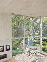 In one corner of the spacious living room the spectacular double height windows allow light to flood the room. A Le Corbusier recliner takes full advantage of the double aspect view.