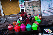 A young boy urinates while his mother fills up water buckets at the water pump in early hours of the day in Vyasarpadi slum in Chennai, Tamil Nadu, India.  Photo by Sanjit Das/Panos