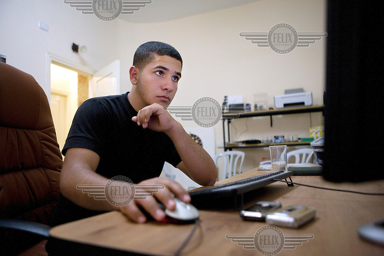 Arafat Kanaan (18) in his home in the Palestinian town of Ni'lin. The town is flanked by the separation barrier and Israeli settlements, cutting it off from the rest of the West Bank. Arafat is a video volunteer who films his daily life with a camera given to him by the Israeli human rights group B?Tselem. With it he records the weekly demonstrations at the separation barrier and in particular he seeks to document human rights abuses by soldiers. ..