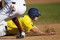 Michigan Wolverines outfielder Jackson Glines (27) slides head first into third base during the NCAA season opening baseball game against the Texas State Bobcats on February 14, 2014 at Bobcat Ballpark in San Marcos, Texas. Texas State defeated Michigan 8-7 in 10 innings. (Andrew Woolley/Four Seam Images)