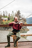 USA, Alaska, Homer, China Poot Bay, Kachemak Bay, one of the employees playing the violin on the dock at Kachemak Bay Wilderness Lodge