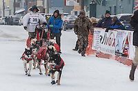 Jason Mackey finished the Iditarod with his son Patrick on the sled inside the finish chute at Nome on Thursday March 13 during the 2014 Iditarod Sled Dog Race.<br /> <br /> PHOTO (c) BY JEFF SCHULTZ/IditarodPhotos.com -- REPRODUCTION PROHIBITED WITHOUT PERMISSION