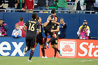 Mexico's Giovani dos Santos leaps into the arms of teammate Andres Guardado after Guardado scored his second goal of the match.  Mexico defeated Costa Rica 4-1 at the 2011 CONCACAF Gold Cup at Soldier Field in Chicago, IL on June 12, 2011.