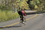 Woman biker racing down Castle Creek Road, near Aspen, Colorado, USA .  John offers private photo tours in Denver, Boulder and throughout Colorado. Year-round.