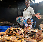 A woman grills fish in her street front stall in Likoni, Kenya.