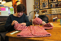 STAFF PHOTO FLIP PUTTHOFF <br /> HAND-MADE GIFT<br /> Rita House works on a knitting project on Saturday Dec. 27 2014 at The Rabbit's Lair fabric and needle-craft store in downtown Rogers. House said she's making a sweater for her granddaughter.