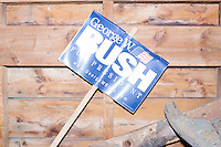 Campaign signs for George W. Bush hange on a wall while Republican presidential candidate and former Florida governor Jeb Bush speaks to a crowd in the barn of Dr. and Mrs. James Betti in Rye, New Hampshire, for former Massachusetts senator Scott Brown's No B.S. BBQ series.