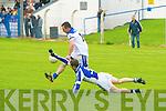 Ballylongford's Liam weir gets the ball away despite the close marking of Templenoe's Joseph Sheehan.