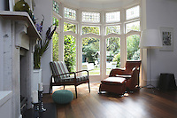 A retro style wooden armchair and a brown leather armchair and footstool are placed in a bay window, which has stained glass in the top lights and gives a view of the garden. The traditional living room has a marble fireplace and a wooden floor. A modern floor lamp standard stands near the window.