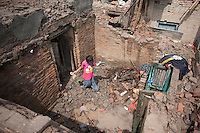 A child recovers belongings from the rubble of her home. Shanku, near Kathmandu, Nepal. May 9, 2015
