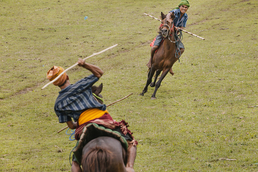Two Pasola warriors throwing the spears at each other from a close range during the event in Wainyapu, Kodi. Pasola is an ancient tradition from the Indonesian island of Sumba. Categorized as both extreme traditional sport and ritual, Pasola is an annual mock horse warfare performed in response to the harvesting season. In the battelfield, the Pasola warriors use blunt spears as their weapon. However, fatal accident still do occurs.