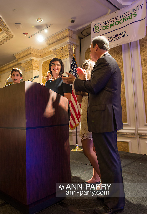 Garden City, New York, USA. 3rd November 2015. Democrat MADELINE SINGAS claims victory over Republican Kate Murray in the hotly contested race for Nassau County District Attorney. JAY JACOBS (at far right), the Chairman of the Nassau County Democratic Party, and Singas's family joined her on stage. Singas, the Acting District Attorney, took the podium at the Nassau County Democrats Election Night Party at the Garden City Hotel, to thank her supporters, when, with more than 99% of the precincts results in, she was comfortably leading Murray, who's Hempstead Town Supervisor.