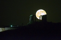 A full moon rises over the temple of Poseidon during the summer solstice in Sounio, Greece. Tuesday 21 June 2016