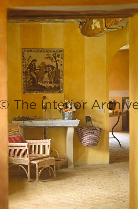 A sepia coloured print hangs above a marble washstand in the hall with a wicker armchair beside it