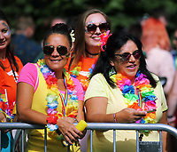 Two women wearing rainbow garlands in the crowd in this year's Pride Parade in the centre of Cardiff, Wales, UK. Sayurday 26 August 2017