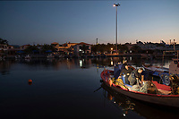 Two fishermen working on boat moored in harbor at dawn, Skala Kallonis, Lesbos, Greece
