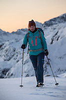 Female hiker in winter mountain landscape, Ytresandheia, Moskenesøy, Lofoten Islands, Norway