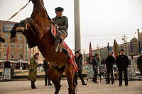A man on a horse poses for a souvenir tourist photo outside the Id Kah Mosque in Kashgar, Xinjiang, China.  In recent years, the local government has retiled the square surrounding the mosque and removed tiles that indicate the direction of Mecca.