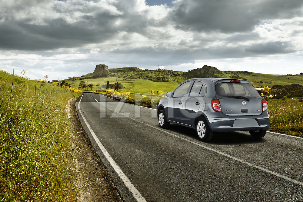 One blue 2011 Nissan Micra Visia Micro Car driving outdoors on country raod.