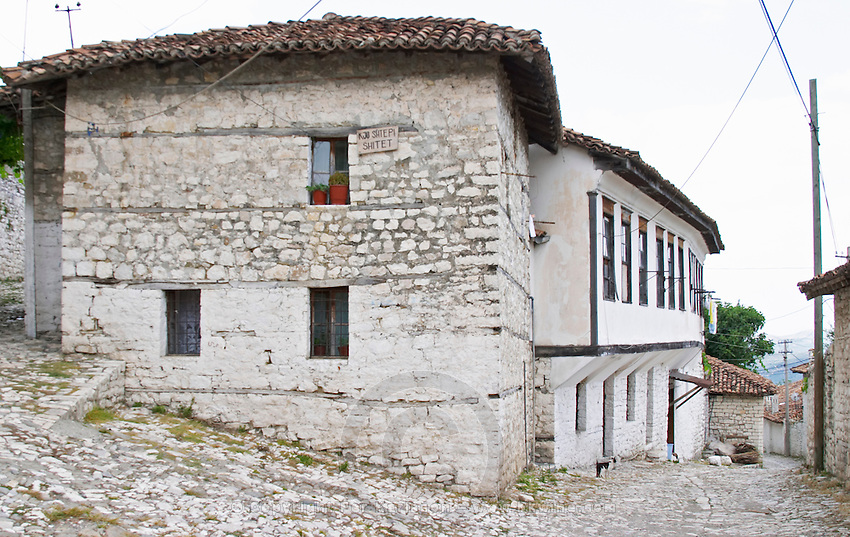 Traditional ottoman white stone houses, cobble stone street. A sign on the house saying that the house is for sale. Berat upper citadel old walled city. Albania, Balkan, Europe.
