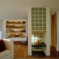 This modern open gas fireplace, with an unusual glass brick chimney, divides the living room
