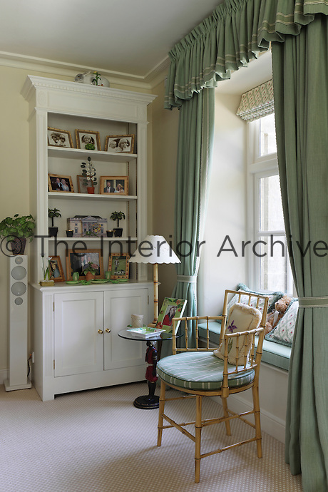 A window seat framed by green curtains in the sitting room